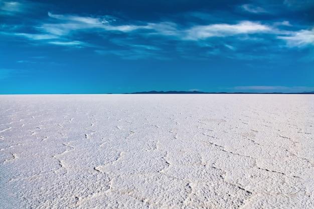 水、塩の平らな砂漠、空の反射で覆われたボリビアのウユニ塩原の風景