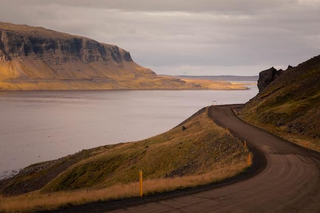 海と東アイスランドを通る道路の風景
