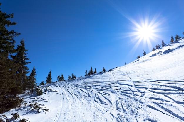 晴れた冬の凍るような日に雪の冬の谷と山と太陽の風景