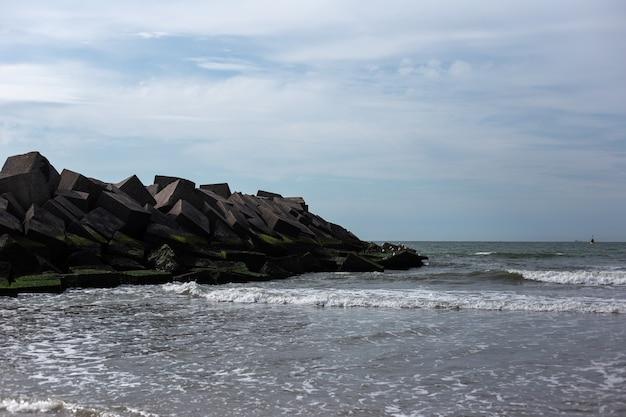 해변에 sunlights와 돌로 큐브의 풍경.