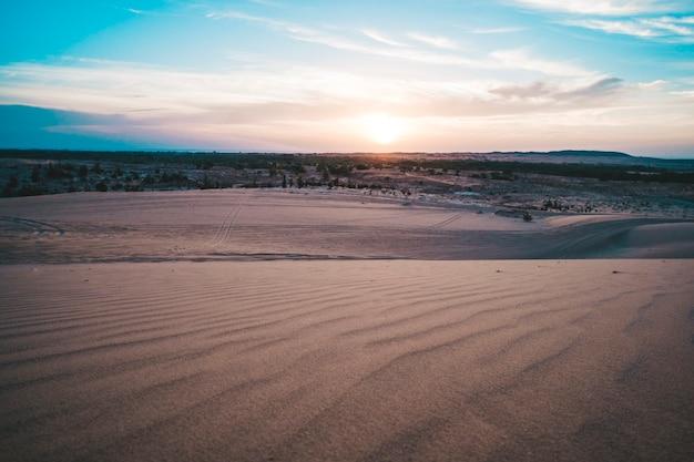 ベトナム、ホワイトサンドデューンズムイネーの砂漠のスカイラインの上の太陽の風景。夕焼けの夜明けの日の出の風光明媚なカラフルな空の下の田園地帯のパノラマ。明るくドラマチックな空の暗い地面の美しい景色