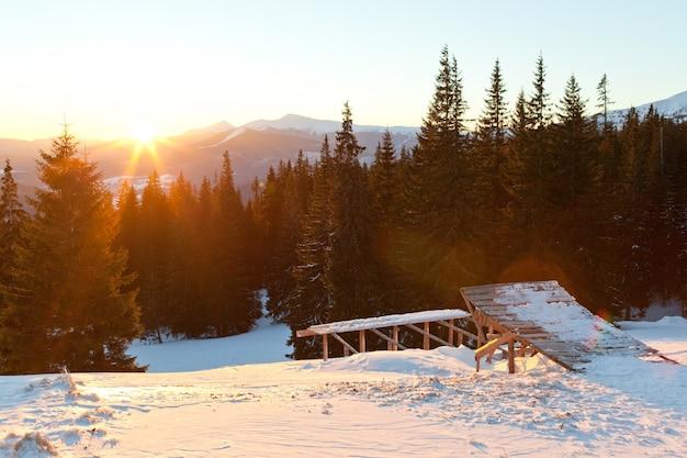 針葉樹の冬の森とスキージャンプの上の夕日の風景