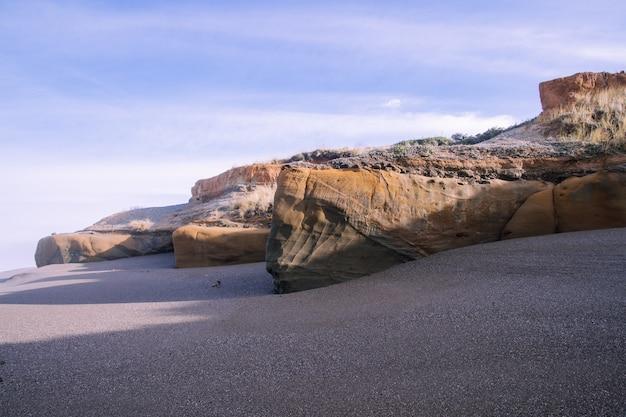 Пейзаж пляжа в окружении скал под солнечным светом и облачным небом в дневное время