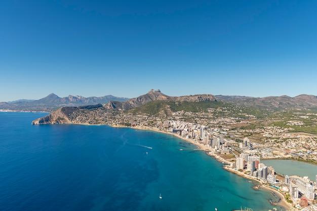 Пейзаж города кальпе с вершины природного парка пеньон-де-ифач с чистым голубым небом.