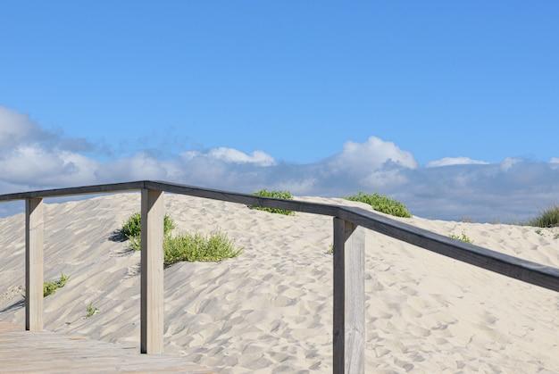 흐린 여름 날에 좋은 하얀 모래와 나무 울타리가있는 포르투갈의 대서양 해변에있는 모래 언덕의 풍경