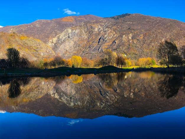 昼間の日光の下で丘や木々が反射した湖の風景