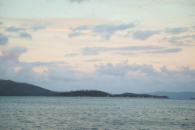 曇り空の下の緑に覆われた丘に囲まれた海の風景