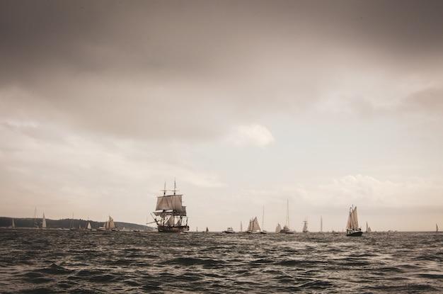 夕方の曇り空の下で帆船が乗っている海の風景