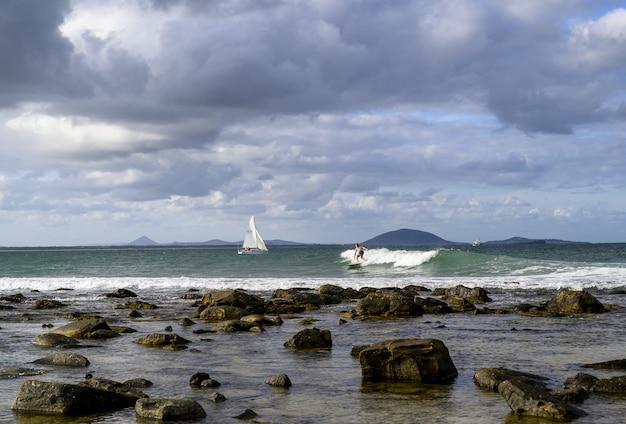 曇り空の下で船とサーファーがいる海に囲まれた海岸の風景