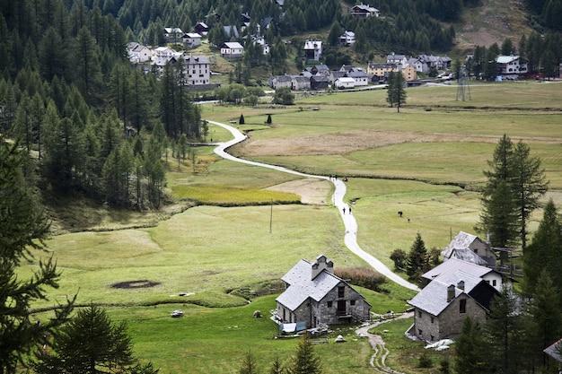 Пейзаж села в окружении холмов, покрытых зеленью в дневное время