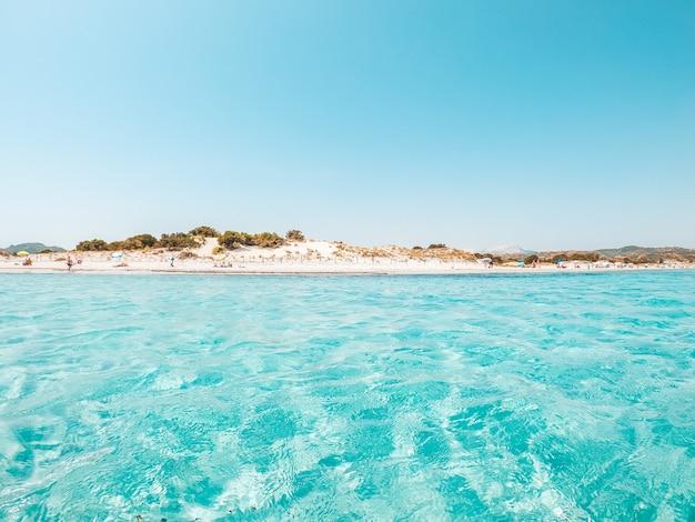 Пейзаж тропического и изумительного пляжа с голубой бирюзовой водой с белым песком.