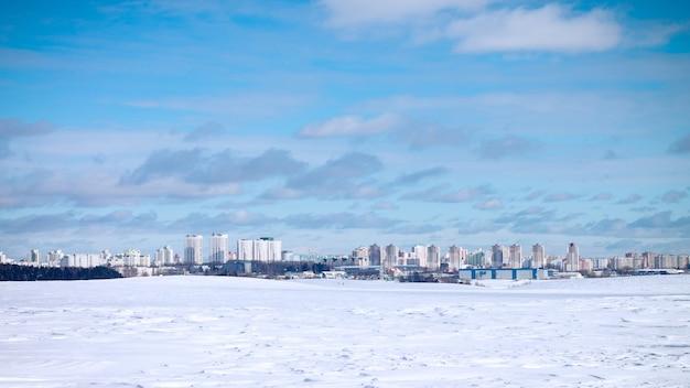 Пейзаж городских высотных зданий, на фоне голубого неба и белого снега
