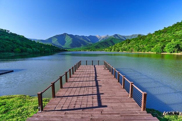 美しい湖と山々の景色を望む木製の桟橋の風景。自然の中で穏やかで静かな平和な雰囲気