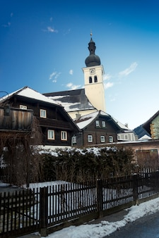 Landscape of old catholic church at austrian village covered by snow