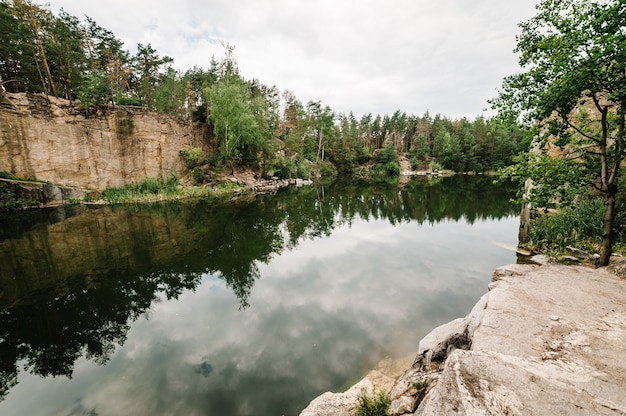 Landscape of an old flooded industrial granite quarry filled with water