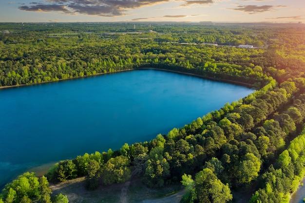 Пейзажная панорама, голубая вода в лесном озере с зелеными лесными деревьями