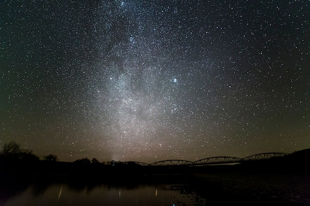 Landscape of pebbles river bank, trees on horizon, bright stars and milky way galaxy in dark sky reflected in quiet water. beauty of nature concept.