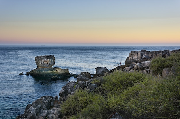 Landscape of people fishing on rocks of the sea cliffs at cascais, portugal