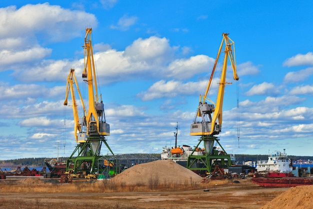 Landscape photo of construction cranes on a background of blue sky, a beautiful picture of an industrial zone