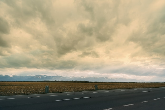 Landscape photo with a part of road, wheat and montains on a cloudy day.