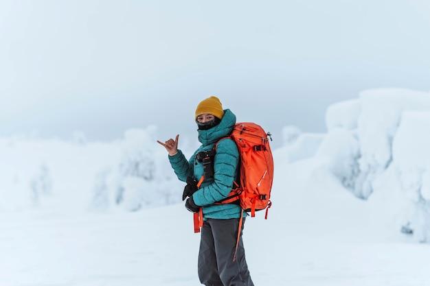 Фотограф-пейзажист делает знак шака на заснеженном пейзаже