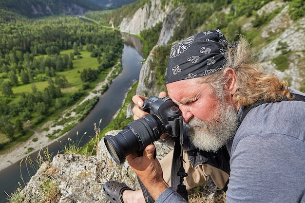 Landscape photographer takes pictures of nature in rocky area, he climbed to top of mountain above calm river.