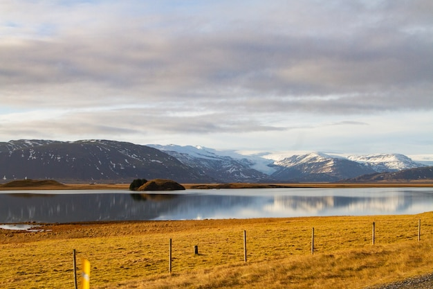 Paesaggio di un fiume circondato da colline coperte di neve e riflettendo sull'acqua in islanda