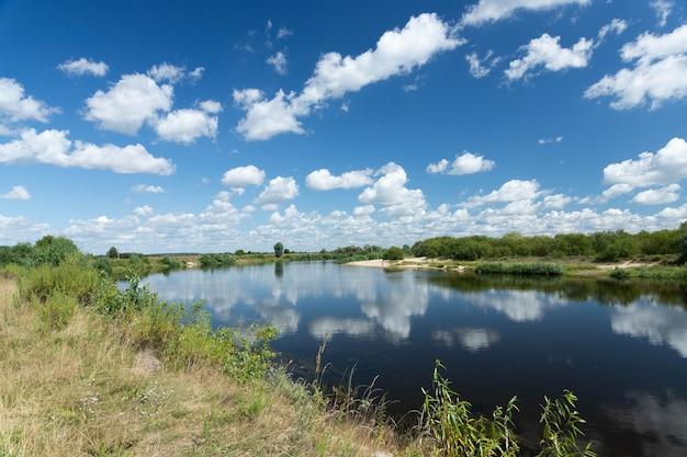 青い空と雲と風景の川は水に反映されます。