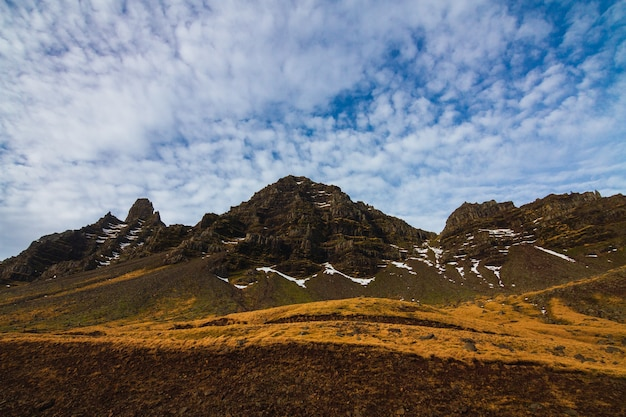 Landscape of rocks covered in greenery and snow under a cloudy sky in iceland