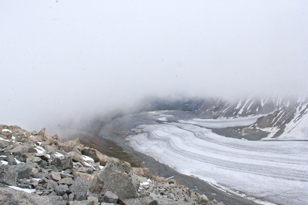 Landscape of rocks covered in the snow and fog at daytime in winter