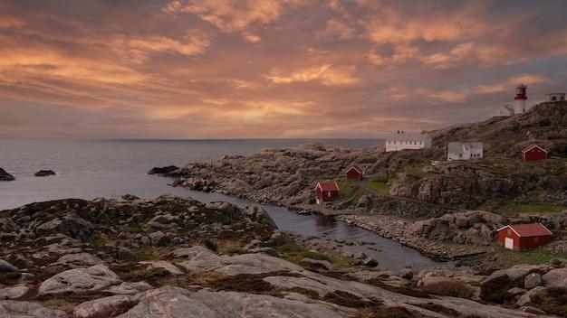 북부 바다의 풍경 바위 해안, 전통적인 목조 빨간색 노르웨이 주택 및 봄 저녁에 노르웨이 남부 등대 lindesnes fyr 노르웨이