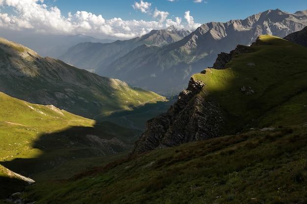 Paesaggio di montagne rocciose coperte di neve sotto la luce del sole e un cielo nuvoloso