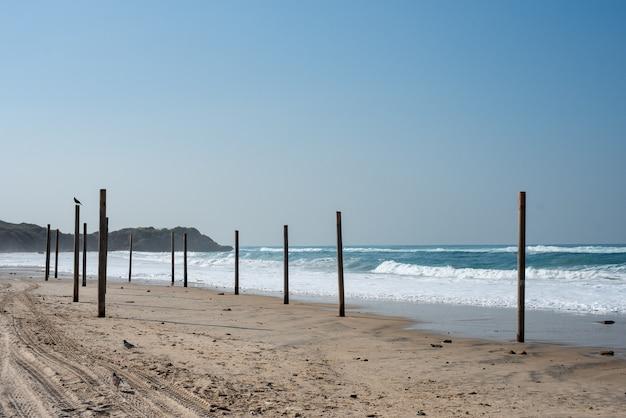 Paesaggio di un mare con colonne di legno su di esso circondato dal mare