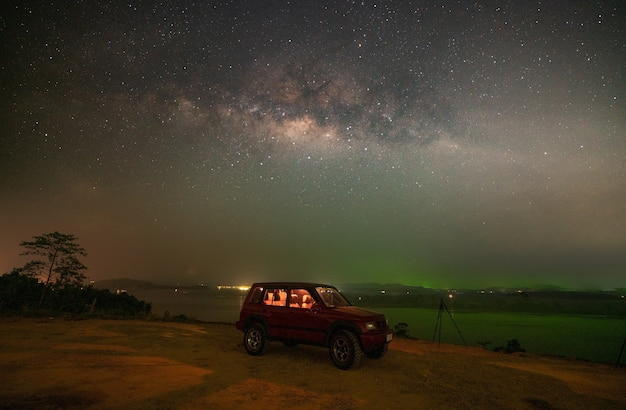 Landscape seascape nature view image of amazing milky way galaxy over sea with 4x4 off road red car in the foreground in night sky at phuket thailand.