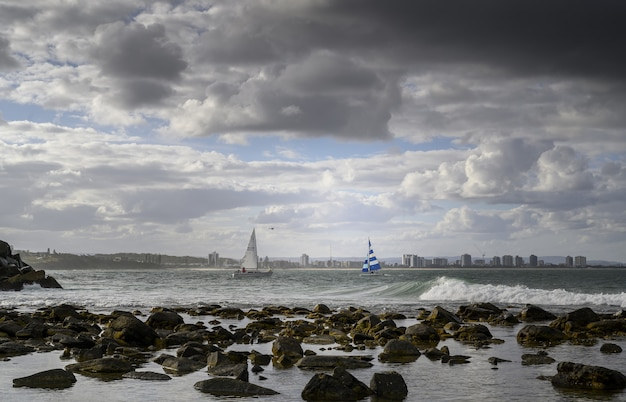 Landscape of the shore surrounded by the sea with ships and surfers on it under a cloudy sky