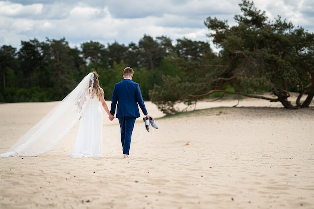 Landscape shot of a couple walking on sand on their wedding day