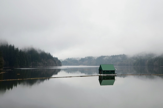Landscape shot of a lake with a small green floating house in the middle during a foggy weather