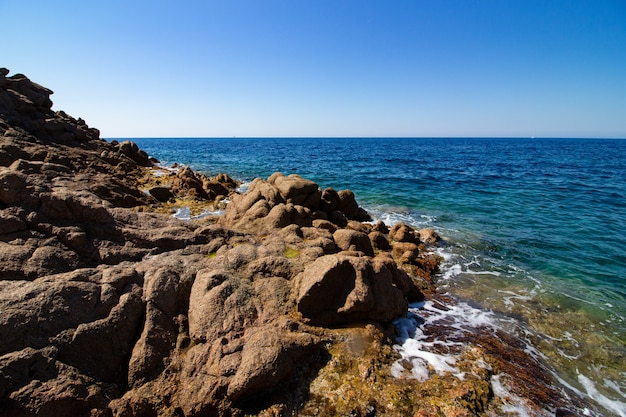 Landscape shot of large bedrocks in an open blue sea with a clear sunny blue sky