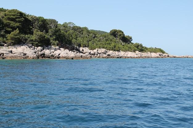 澄んだ青い空と青い水の中の緑の丘の風景ショット