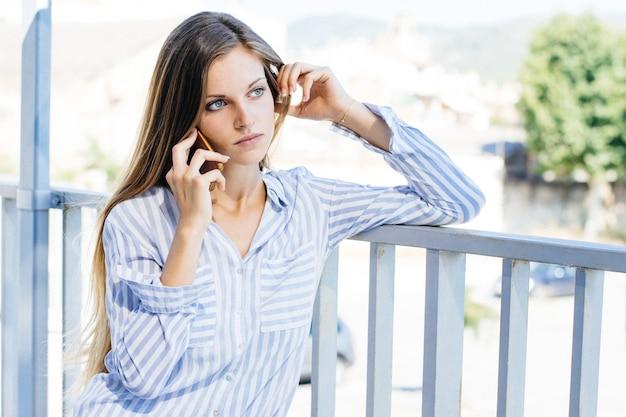 電話で話している縞模様の白と青のシャツを着た若い女性の風景写真