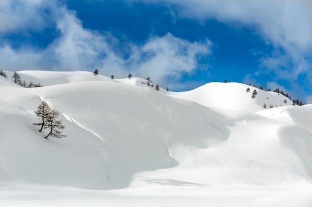 Пейзажный снимок холмов, покрытых снегом в пасмурном голубом небе