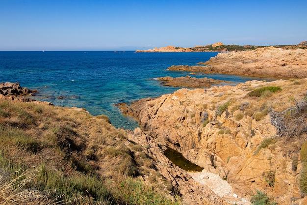 澄んだ青い空と開いた青い海の岩だらけの丘の風景写真