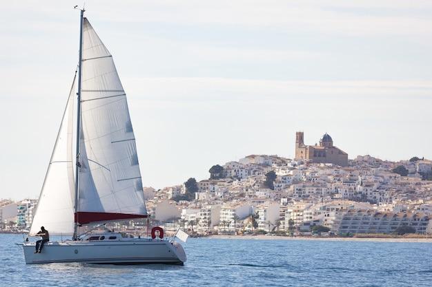 Landscape shot of a sailboat near the port