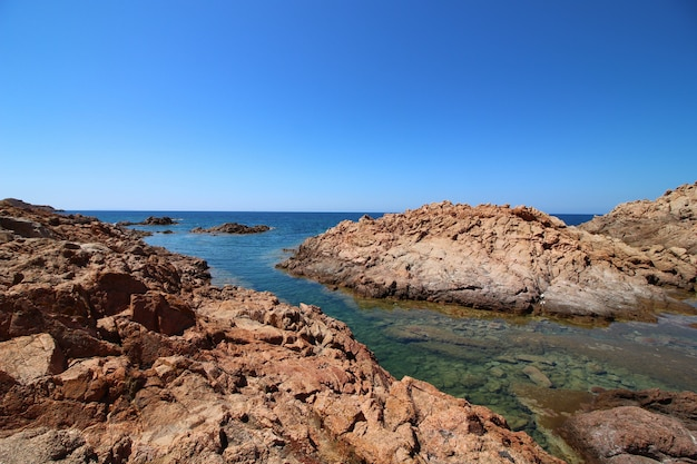 Landscape shot of a seashore with big rocks in a clear blue sky