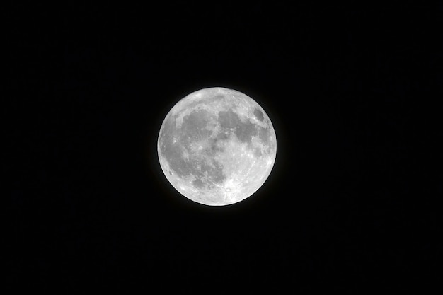 Landscape shot of a white full moon with black color in the background