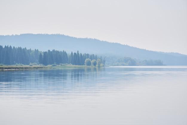 Пейзаж - силуэты лесистых холмов на берегу широкой реки в дымке и нежном утреннем свете.