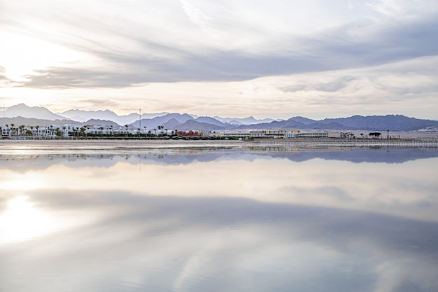 The landscape sky is reflected in the sea. city coastline with mountains on the horizon.