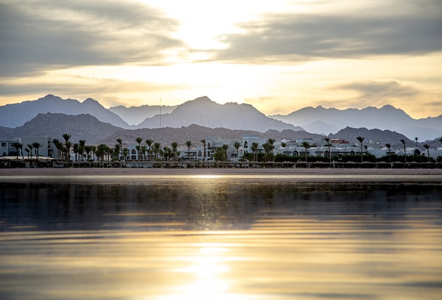 The landscape sky is reflected in the sea in the setting light. city coastline with mountains on the horizon.