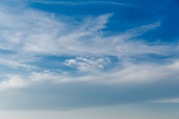 Landscape of stretched clouds of white light against a blue sky