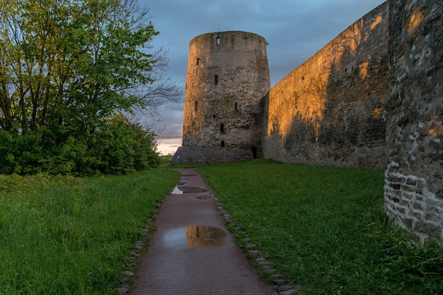 Landscape at sunset. the medieval wall of the izborsk fortress. pskov region, russia